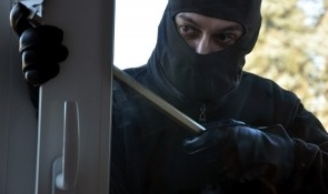 Burglar breaking and entering a house with a crowbar